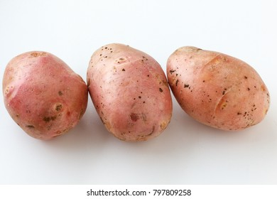 A lot of dirty potatoes on a white background. Potatoes scattered on a white background.