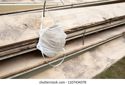 Dirty protective mask hanging on nail with pile of old wooden plank. Dust, Pollution protection work concept.
