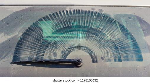 dirty rear car windowwith wiper and dust