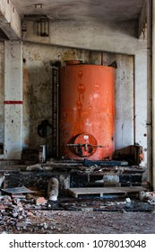 Dirty red oil tank inside abandoned building