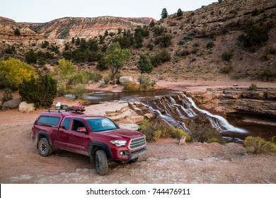 A dirty red truck with camper shell, propane tank, ammo boxes, gas can, and firewood on the roof. The truck sits on a rough, rocky trail near a waterfall on the red rock sandstone of Southern Utah.