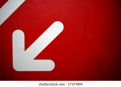 dirty red wall with white arrow