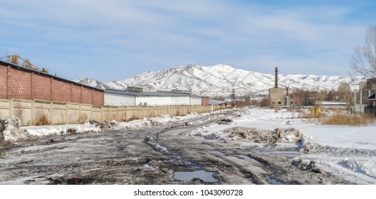 Dirty road in the industrial zone. Spring. Slush. Industrial landscape. Industrial zone. Old factory
