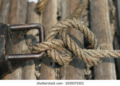Dirty rope bind steel hook with stack bamboo background in day light