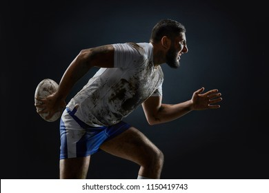 Dirty rugby player with rugby ball on dark background. Portrait