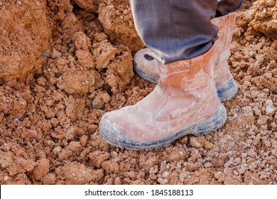 Dirty safety boots are being worn by construction workers in earthworks.