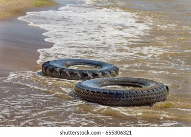 Dirty sea beach. Garbage on beach. Old rubber wheels, car tires pollute beach. Pollution of natural ecosystem. Ecological problem. Conceptually pollution of nature with waste of civilization