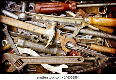 Dirty set of hand tools on a wooden panel/vintage background with a tools