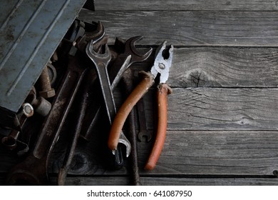 Dirty set of hand tools on a wooden background Old rusty Equipment for locksmith and metalworking shop Old shop Old working tools. Vintage working tools drill saw ruler and others on wooden background