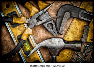 Dirty set of hand tools on a wooden panel