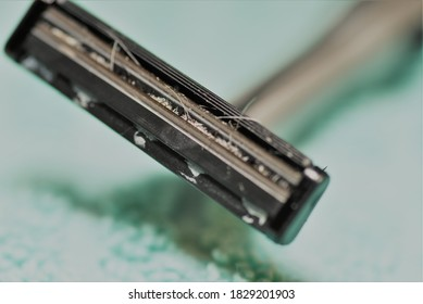 schmutziger Rasiermesser mit zwischen den Blades festgeklemmtem Haar