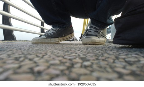 Dirty shoes and a woman's background behind