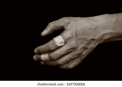 The dirty, sinewy male hand of a workman. Bandaged damaged fingers on a black, isolated background. The concept of hard work of a miner, mechanic, worker. Copy space, space for text.