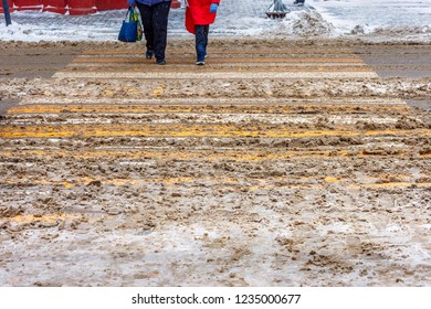 The dirty snow-covered uncleaned crosswalk with two people crossing the road at the winter time.