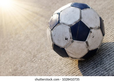 Dirty soccer ball isolated on concrete road