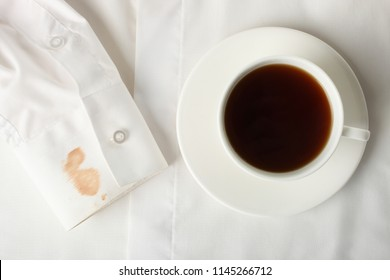 Dirty spot on the sleeve of white shirt and cup of tea.