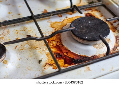 Dirty stove with food leftovers. Unclean gas kitchen cooktop with greasy spots, old fat stains, fry spots and oil splatters.