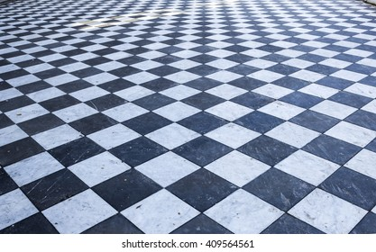 Dirty street floor of black and white marble tiles forming a checkerboard pattern
