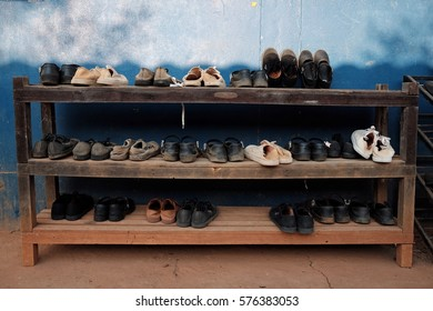 Lot of dirty students shoes on rack