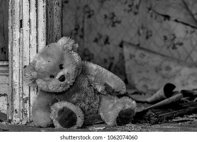 A dirty teddy bear leaning against a door frame in an old, abandoned house. Debris and assorted wallpaper peeling from the wall in the background. Black and white.