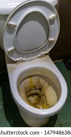 Dirty toilet bowl with yellow limescale stain in a house. Unhygienic, unclean and unpleasant toilet.