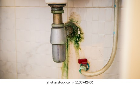 Dirty toilet with stains and lichen in joint of tube under the sink, water flow drainage system, dirty faucet on white wall.