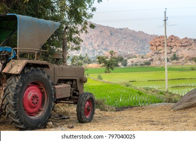 A dirty tractor in front of a rice field in rural India.