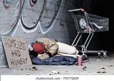 Dirty tramp lying on blanket next to a sign and trolley in the shelter of the city