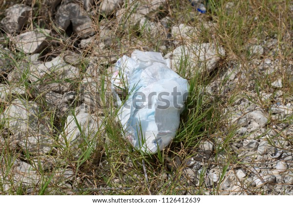 Dirty trash diaper left on bank at Amistad Lake shore on rocks.