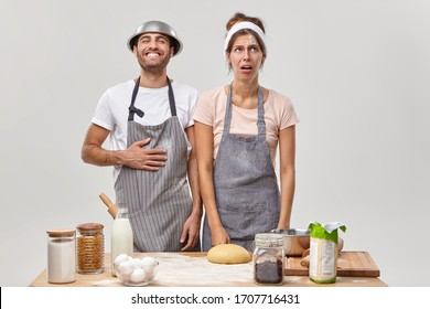 Dirty unhappy housewife feels tired after rolling out dough, happy funny man wears bowl on head and apron, stand at table with ingredients, bake cake or cookies in kitchen at home, pose indoor