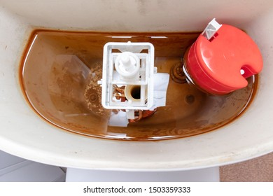 Dirty unhygienic rusty and calcified flush tank of toilet with limescale and rust stains and scum need to be cleaned and repared.