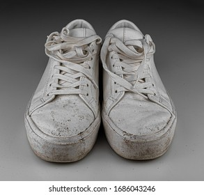 Dirty, used, muddy white dirty pair of shoes on white dirty floor