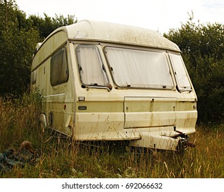 Dirty white caravan in a British field with long grass and weeds