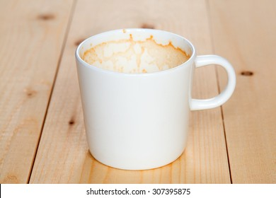 Dirty white mug of coffee lying on the boards