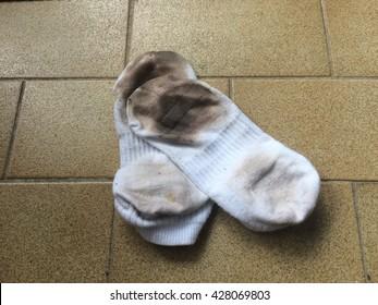 Dirty white socks on the dirty floor