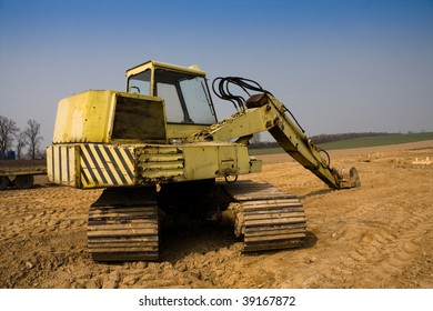 Dirty yellow excavator on construction site