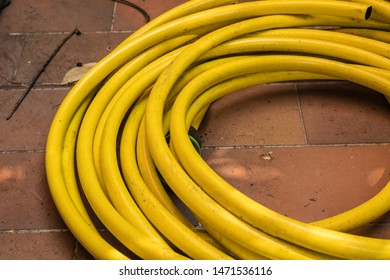 Dirty yellow hosepipe on the brick floor, garden hose for irrigation closeup - Image