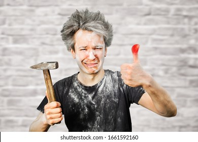 Dirty young builder guy fail is hold a hammer, hit the finger on brick wall background at home during repairs.