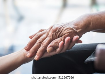 Disability awareness day, aging society concept with Parkinson disease,  Alzheimer patient, elderly senior citizen person's hand with Arthritis pain in nursing family care giving of caregiver support