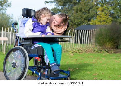 Disability a disabled child in a wheelchair relaxing outside together with a carer / Disability a disabled child relaxing outside with a carer