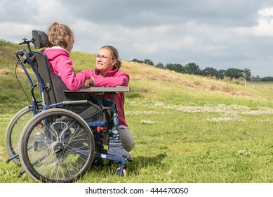 Disability a disabled child in a wheelchair relaxing outside in the playground with a carer / Disability a disabled person in a wheelchair