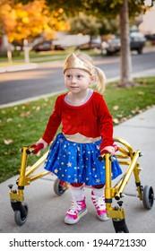 Invaliditätsfoto eines süßen kleinen behinderten Mädchens, das mit einem speziellen Spaziergänger auf dem Bürgersteig geht