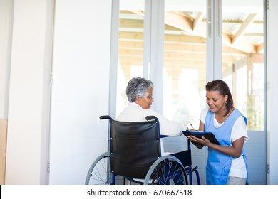 Disability senior woman discussing with female doctor at home
