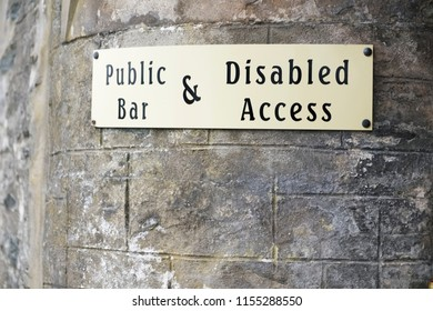 Disabled access sign on stone wall at public bar pub entrance