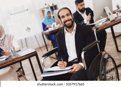 Disabled arab man in suit in wheelchair working in office. Man is taking notes.