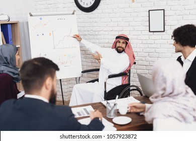 Disabled arab man in thawb in wheelchair working in office. Man is showing charts on whiteboard.