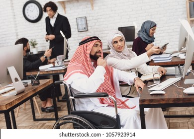 Disabled arab man in thawb in wheelchair working in office. Man is discussing work with female coworker.