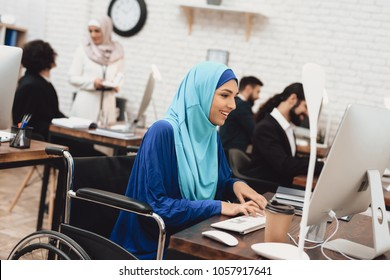 Disabled arab woman in hijab in wheelchair working in office. Woman is working on desktop computer.