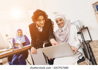 Disabled arab woman in hijab in wheelchair working in office. Woman is talking to male coworker.
