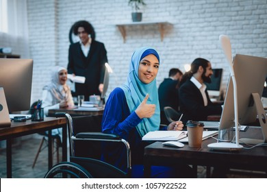 Disabled arab woman in hijab in wheelchair working in office. Woman is giving thumbs up.